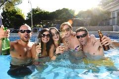 愉快的可爱的男人和妇女比基尼泳装的有浴在旅馆手段游泳池饮用的啤酒 免版税库存图片