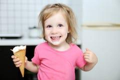 愉快的可爱的矮小的小孩女孩在家吃冰淇凌 图库摄影