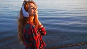 愉快的可爱的红发女孩享受在步行的喜爱的音乐 衬衣的美丽的少妇使用耳机 免版税库存照片