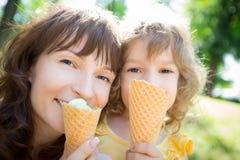 愉快的吃冰淇凌的孩子和母亲 免版税库存图片