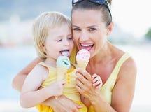愉快的吃冰淇凌的母亲和婴孩 免版税图库摄影