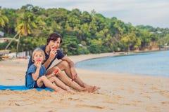 愉快的吃在海滩的家庭父亲和儿子一个西瓜 孩子吃健康食物 免版税库存照片
