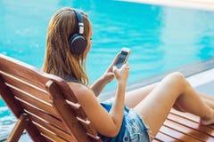 愉快的听与earbuds的智能手机妇女松弛近的游泳池放出音乐 使用她的流动响度单位的美丽的女孩 库存照片