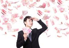 愉快的商人举行中国金钱 免版税库存图片