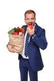 愉快的商人举行袋子用健康食物,杂货买家被隔绝 免版税库存图片