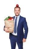 愉快的商人举行袋子用健康食物,杂货买家被隔绝 图库摄影