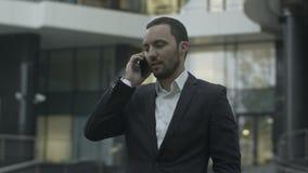 愉快的商人回答的电话和谈话与 影视素材