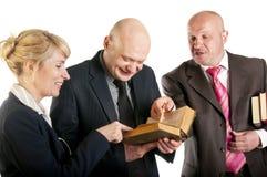 愉快的商人在会议的读一本旧书 免版税库存照片
