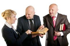 愉快的商人在会议的读一本旧书 库存照片
