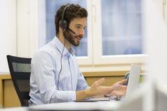 愉快的商人在电话的办公室,耳机, Skype 免版税库存照片