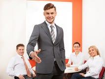 愉快的商人提供的握手和他的队画象  免版税库存照片