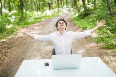 愉快的商人用被举的手庆祝了不起的工作或好消息在膝上型计算机前面在办公桌在绿色公园 事务 免版税库存图片