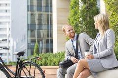 愉快的商人谈话与女性同事在城市 库存照片