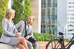 愉快的商人谈话与女性同事在城市 免版税库存照片