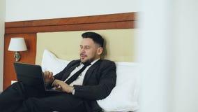 愉快的商人谈话与家庭通过网上录影闲谈使用说谎在床上的便携式计算机在旅馆客房 旅行 股票录像