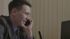 愉快的商人谈话在智能手机在办公室 股票录像