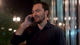 愉快的商人谈话在电话在晚上 影视素材