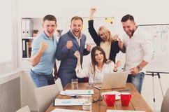 愉快的商人队在办公室庆祝成功 免版税图库摄影