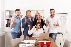 愉快的商人队在办公室庆祝成功 免版税库存图片