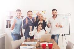 愉快的商人队在办公室庆祝成功 库存照片