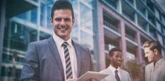愉快的商人画象与同事的在办公室外 免版税库存图片