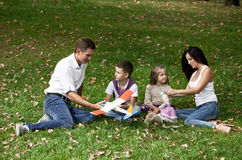 愉快的四口之家,休息在秋天公园 库存照片