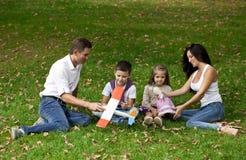 愉快的四口之家,休息在秋天公园 免版税库存图片