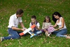 愉快的四口之家,休息在秋天公园 免版税库存照片