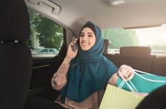 愉快的回教妇女谈话在汽车的智能手机 免版税库存照片