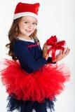 愉快的圣诞老人女孩拿着有红色的礼物盒 图库摄影