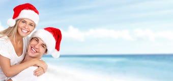 愉快的圣诞节在海滩的圣诞老人夫妇。 免版税库存照片