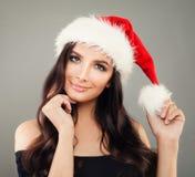 愉快的圣诞节妇女在红色圣诞老人帽子的时装模特儿 免版税库存照片
