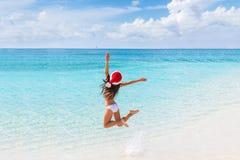 愉快的圣诞节帽子女孩跳跃在海滩的喜悦 免版税库存图片