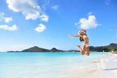 愉快的圣诞节帽子女孩跳跃在海滩的喜悦 库存照片