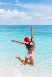 愉快的圣诞节帽子女孩跳跃在海滩的喜悦 库存图片