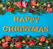 愉快的圣诞节金黄文本和云杉的分支和圣诞节deco 免版税库存图片