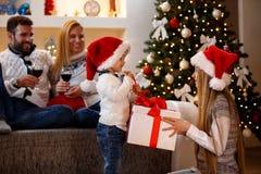 愉快的圣诞节-打开圣诞节礼物的孩子 免版税库存照片