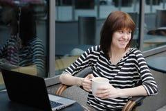 愉快的在一个室外咖啡馆的女孩饮用的咖啡 库存图片