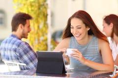 愉快的在一种片剂的妇女观看的录影在咖啡店 免版税库存照片