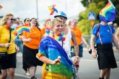 愉快的在人群的妇女佩带的彩虹旗子在斯德哥尔摩骄傲游行期间 免版税图库摄影