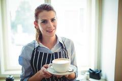 愉快的在咖啡馆的女服务员提供的咖啡画象  免版税库存图片