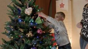 愉快的在圣诞树的男孩垂悬的姜饼与母亲 股票录像