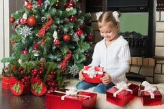 愉快的在圣诞树附近的女孩开放红色礼物盒 库存图片