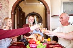 愉快的在圣诞节的家庭欢呼的玻璃在被弄脏的背景 感恩晚餐 庆祝概念 免版税库存照片