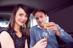 愉快的在大型高级轿车的夫妇饮用的香槟 库存图片
