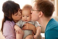 愉快的在家亲吻小儿子的母亲和父亲 免版税库存照片