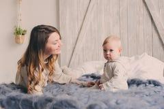 愉快的在家使用在卧室的母亲和婴孩 舒适家庭生活方式 库存图片