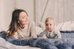愉快的在家使用在卧室的母亲和婴孩 舒适家庭生活方式 免版税库存照片