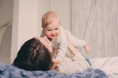 愉快的在家使用在卧室的母亲和婴孩 舒适家庭生活方式 免版税库存图片