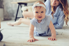 愉快的在家使用在卧室的母亲和婴孩 免版税图库摄影